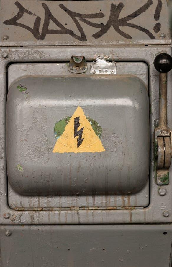 Viejo interruptor de alto voltaje eléctrico con una muestra pintada del peligro Fondo abstracto del peligro fotos de archivo