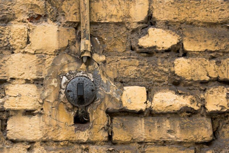 Viejo interruptor de la luz de la calle en una pared de ladrillo amarilla fotos de archivo
