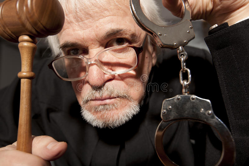 Viejo juez masculino en una sala de tribunal que pega el mazo fotos de archivo libres de regalías