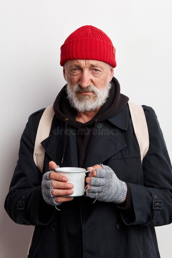 Viejo mendigo barbudo encubierto en ropa negra sosteniendo una taza de té caliente para calentarse en un día frío foto de archivo libre de regalías
