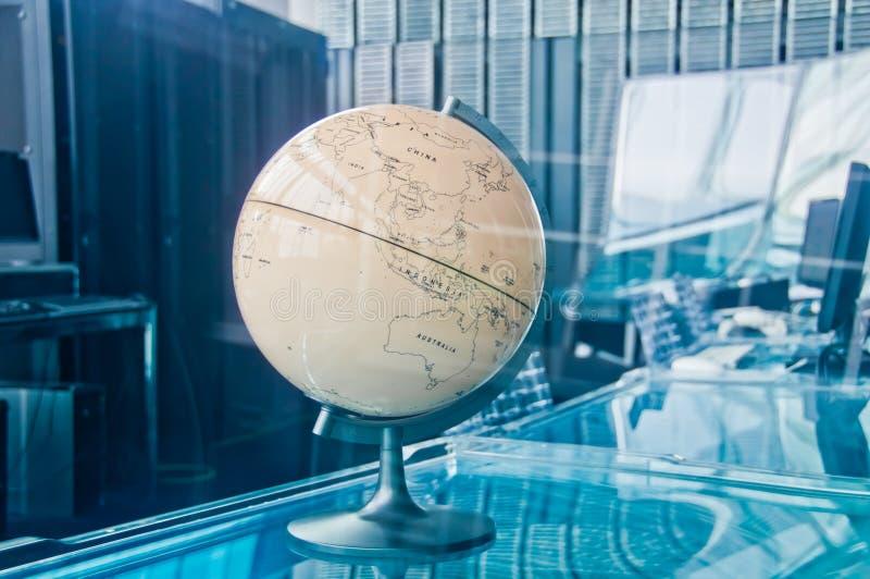 Viejo modelo retro cl?sico del globo de la tierra del vintage en un cuarto ejecutivo de la gesti?n del tablero de operaci?n de la imagen de archivo