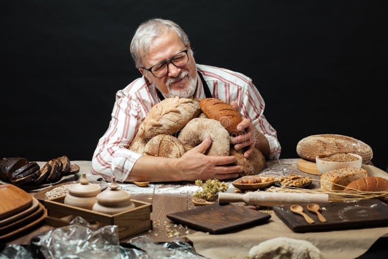 Viejo panadero feliz que mira la cámara y que sonríe mientras que abraza las barras de pan imagen de archivo libre de regalías