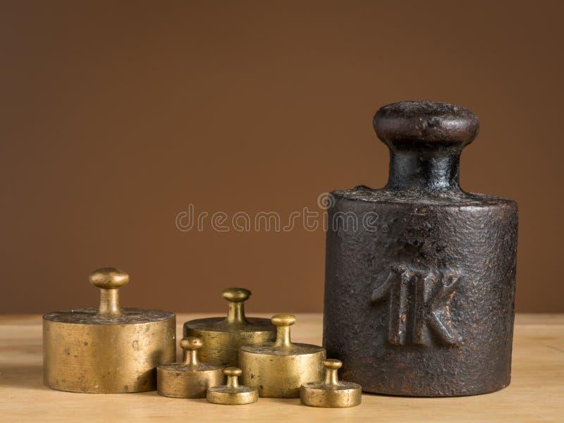 Viejo peso del hierro 1kg y pesos de cobre amarillo más pequeños para una escala de la cocina foto de archivo libre de regalías