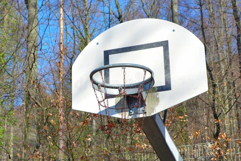 Viejo plumón funcionado con y cesta oxidada del baloncesto en la tierra del juego rodeada por el bosque fotografía de archivo