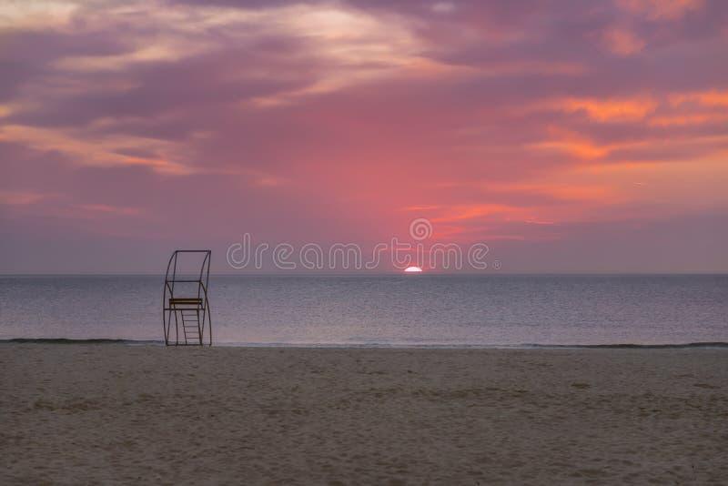 Viejo poste del rescate en la playa en la puesta del sol fotografía de archivo libre de regalías