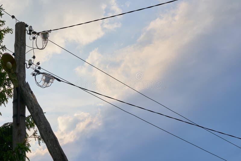 Viejo poste eléctrico de madera de la calle con los alambres en fondo del cielo fotografía de archivo