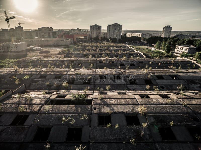 Viejo rooof abandonado con los agujeros de la ventana y la vista de la ciudad fotografía de archivo