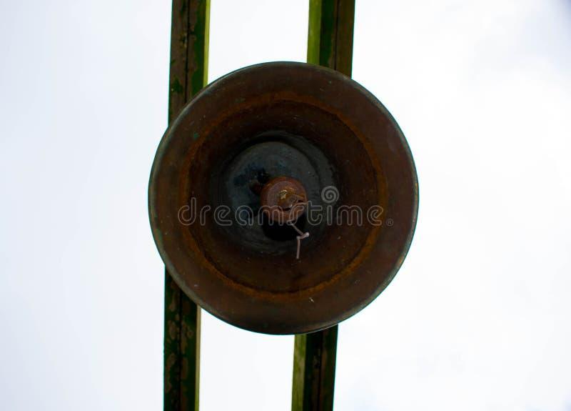 Viejo Rusty Bronze Bell Hanged en el tablón de madera cubierto de musgo dos imágenes de archivo libres de regalías
