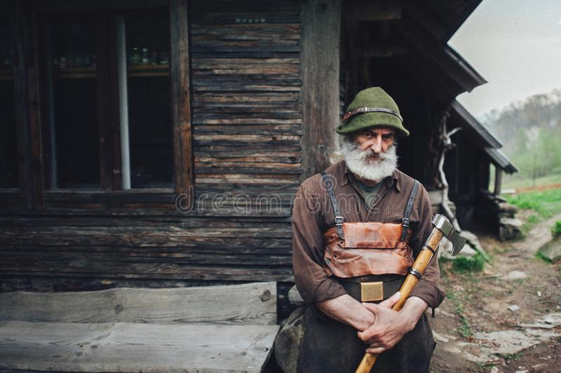 Viejo silvicultor barbudo con el hacha cerca de la choza de madera imagenes de archivo