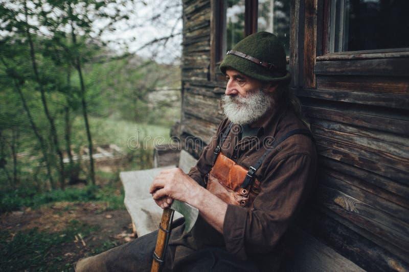Viejo silvicultor barbudo con el hacha cerca de la choza de madera foto de archivo libre de regalías