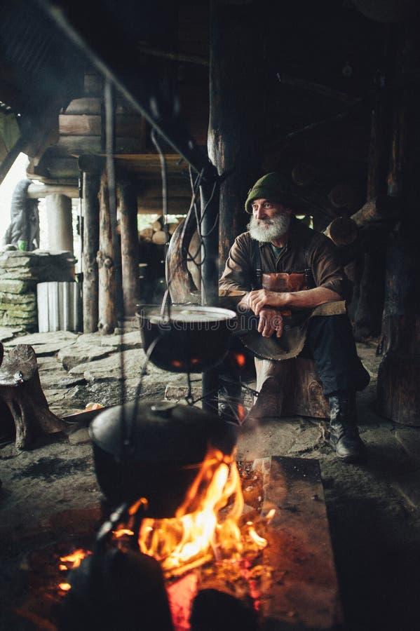 Viejo silvicultor barbudo con el hacha cerca de la choza de madera imagen de archivo