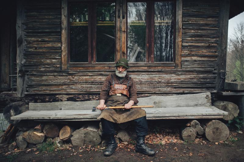 Viejo silvicultor barbudo con el hacha cerca de la choza de madera fotos de archivo