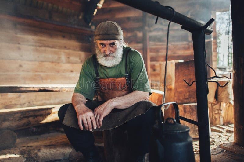 Viejo silvicultor de la barba en el peto que se sienta en granero fotos de archivo