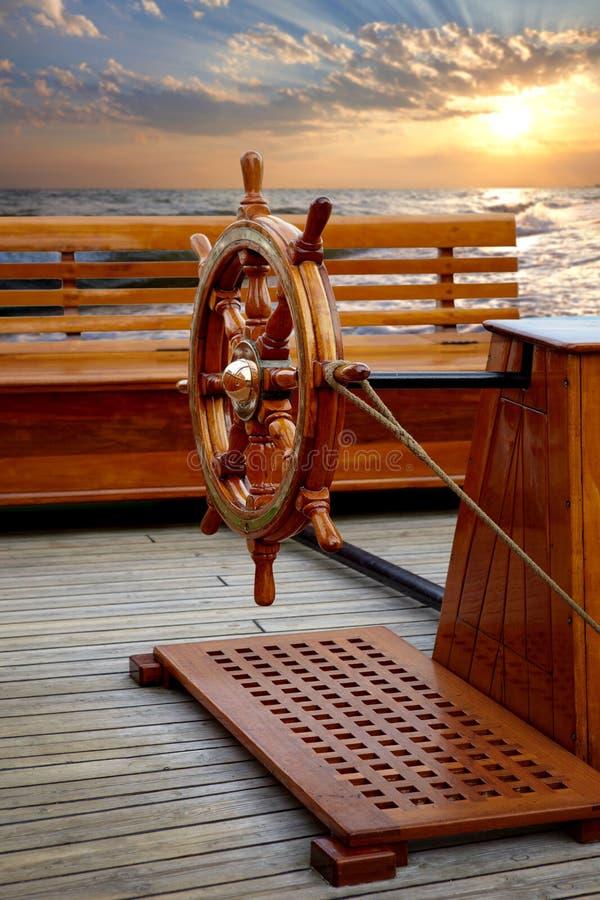 Viejo timón de barco de madera sobre el fondo de la puesta de sol del mar imágenes de archivo libres de regalías