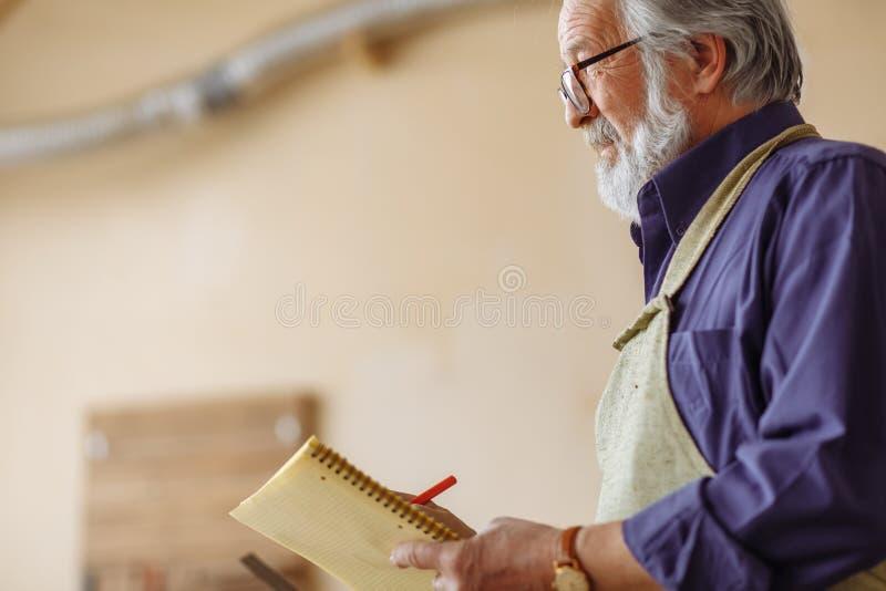 Viejo trabajador con la barba del nad del bigote que sostiene la libreta imagen de archivo libre de regalías