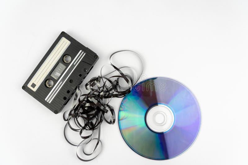 Viejo vintage y casete compacto con la cinta que se pega hacia fuera y un Cd del disco compacto imagenes de archivo