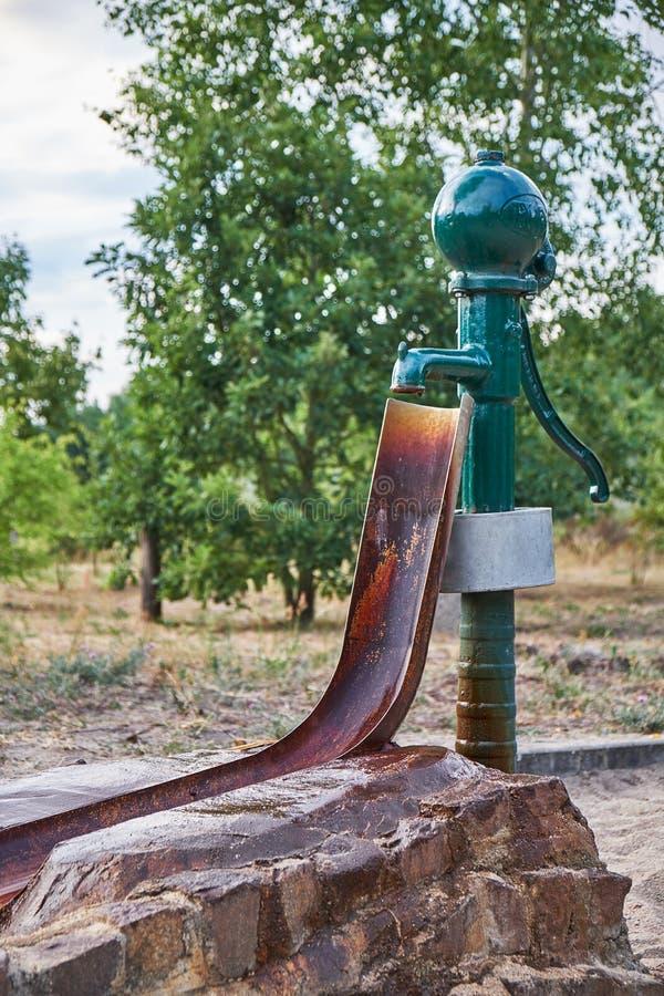 Viejo waterpump hecho del acero con un conectado mediante canales oxidado donde el agua catched fotografía de archivo