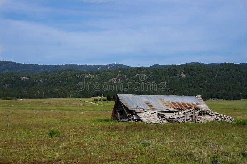 Viejo y resistido a casa derrumbado y silencioso en el campo olvidado fotos de archivo