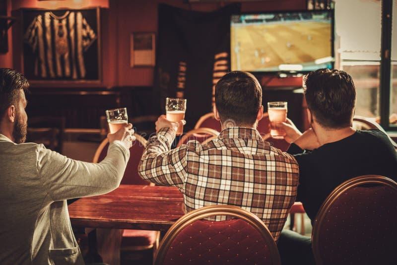 Viejos amigos alegres que miran deportes y que beben la cerveza de barril en pub fotos de archivo