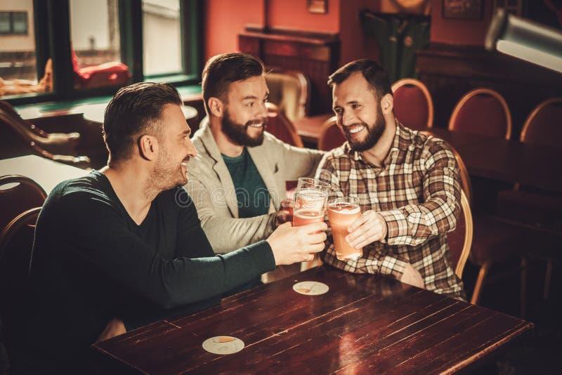 Viejos amigos alegres que se divierten y que beben la cerveza de barril en pub foto de archivo libre de regalías