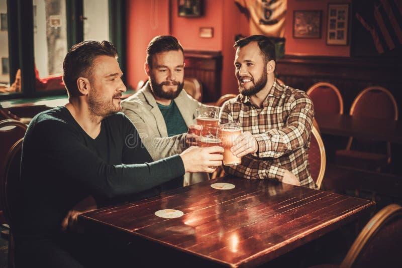 Viejos amigos alegres que se divierten y que beben la cerveza de barril en pub imagen de archivo