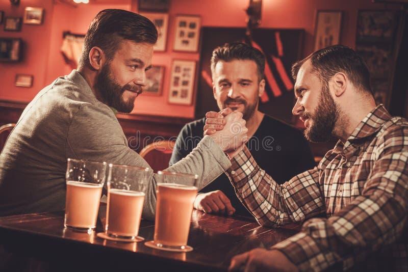 Viejos amigos alegres que tienen desafío del pulso en un pub fotos de archivo