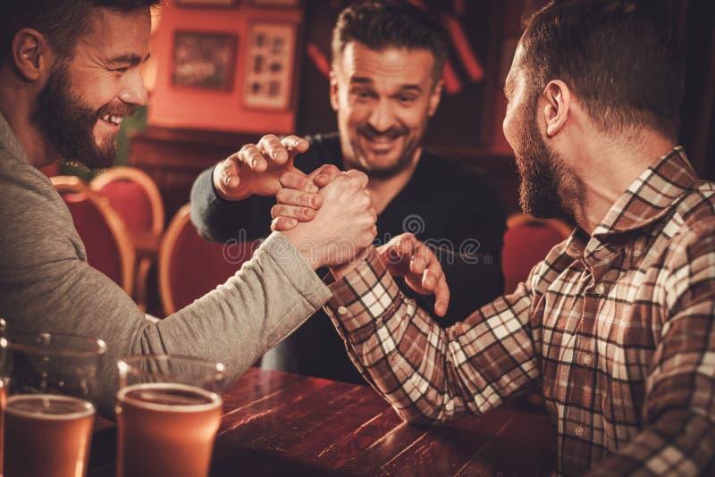 Viejos amigos alegres que tienen desafío del pulso en un pub fotografía de archivo libre de regalías