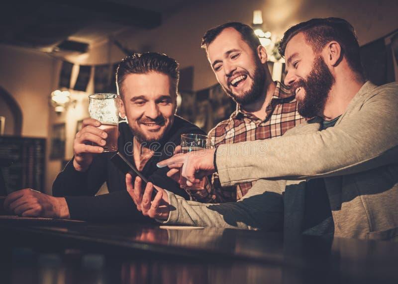 Viejos amigos que se divierten con smartphone y que beben la cerveza de barril en el contador de la barra en pub imagen de archivo libre de regalías