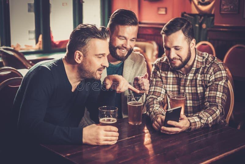 Viejos amigos que se divierten con smartphone y que beben la cerveza de barril en pub imagen de archivo