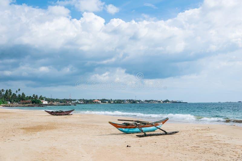 Viejos barcos catamarán en la playa contra el océano y cielo azul con hermosas nubes en un día soleado, Sri Lanka fotos de archivo