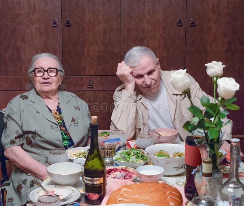 Viejos cónyuges en la tabla después de la cena festiva foto de archivo libre de regalías