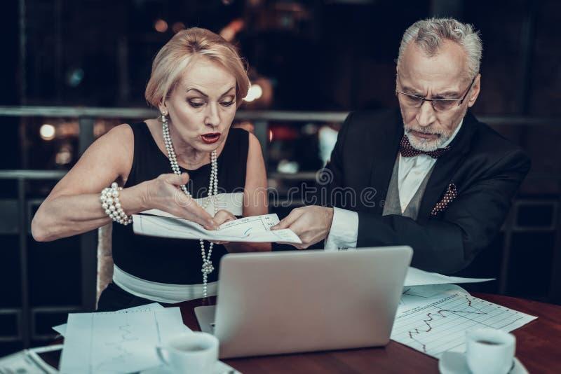 Viejos hombres de negocios que miran gráficos foto de archivo