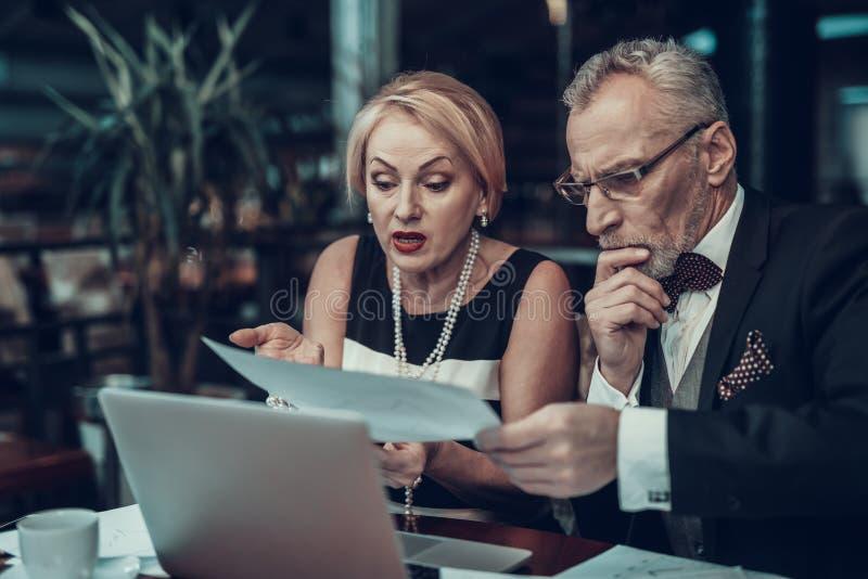 Viejos hombres de negocios que miran gráficos fotografía de archivo libre de regalías