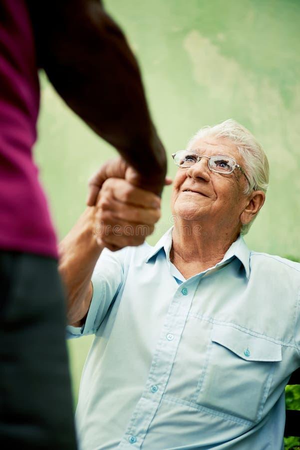 Viejos hombres negros y caucásicos que hacen frente y que sacuden a las manos en parque imágenes de archivo libres de regalías