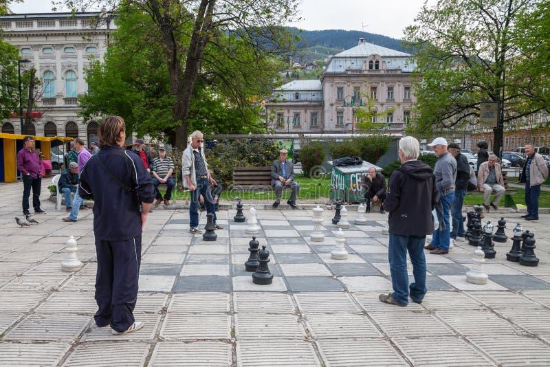 Viejos hombres que juegan a un juego gigante de ajedrez en el centro de ciudad de Sarajevo, capital de Bosnia imagen de archivo