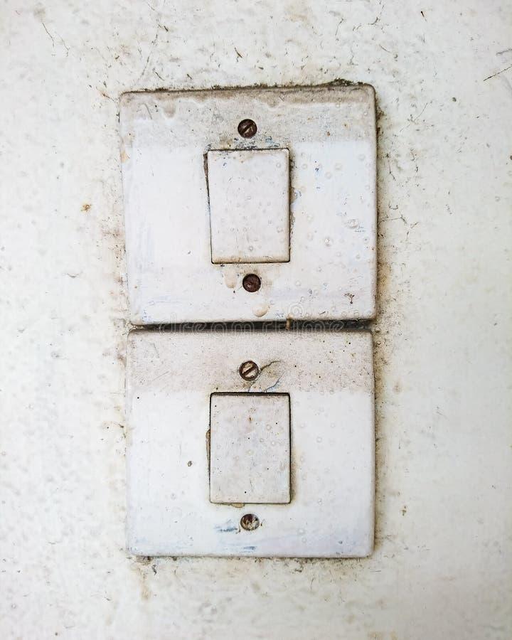 Viejos interruptores sucios en la pared blanca foto de archivo libre de regalías