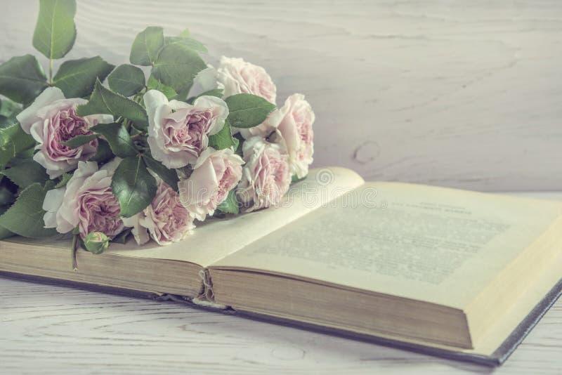 Viejos libro y manojo abiertos de flores color de rosa del inglés rosado foto de archivo libre de regalías