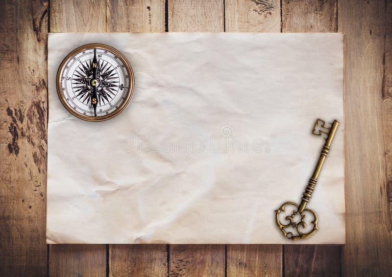 Viejos llave y comp?s en viejo vintage de papel en el fondo de madera con el espacio fotografía de archivo