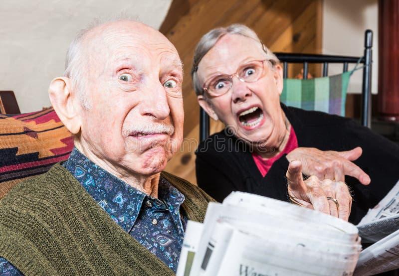 Viejos pares enojados con el periódico imagen de archivo libre de regalías