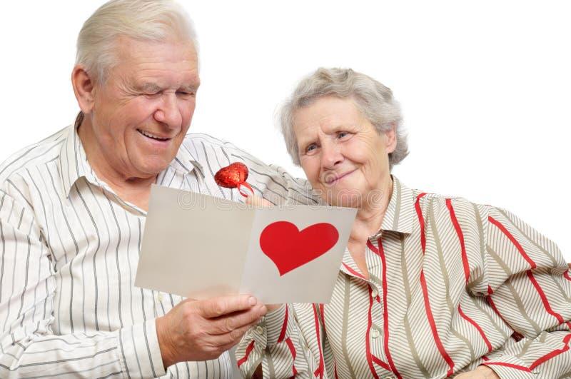 Viejos pares felices con la postal fotos de archivo