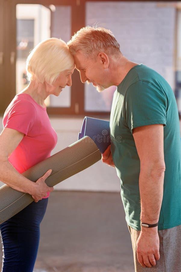 Viejos pares felices con las esteras de la yoga que tocan las frentes imagen de archivo