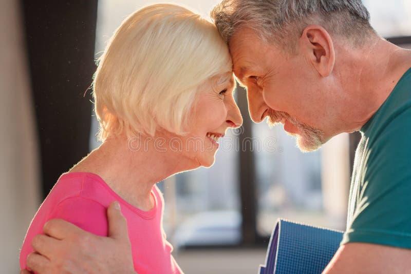 Viejos pares felices con las frentes conmovedoras de la estera de la yoga fotos de archivo libres de regalías