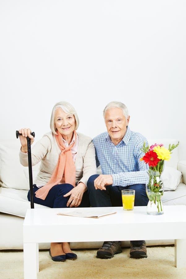 Viejos pares mayores en un sofá foto de archivo