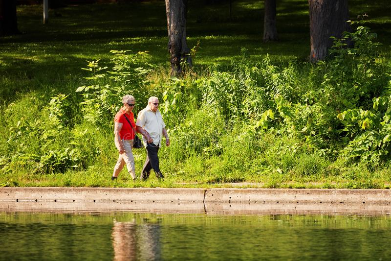 Viejos pares que caminan de común acuerdo cerca de la charca en el La Fontaine del parque imagen de archivo