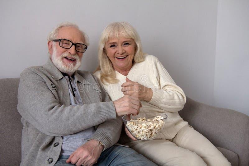 Viejos pares que comen las palomitas en el sofá imágenes de archivo libres de regalías