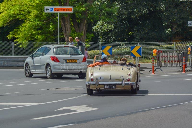 Viejos pares que conducen el coche clásico imagen de archivo libre de regalías
