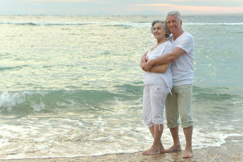 Viejos pares que corren en la playa del mar imágenes de archivo libres de regalías