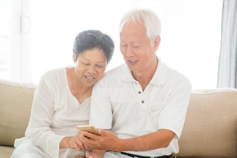 Viejos pares usando los teléfonos elegantes fotos de archivo libres de regalías