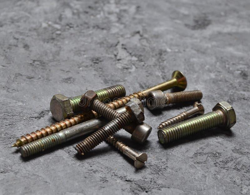 Viejos pernos oxidados, tornillos penetrantes en una superficie concreta imagen de archivo libre de regalías
