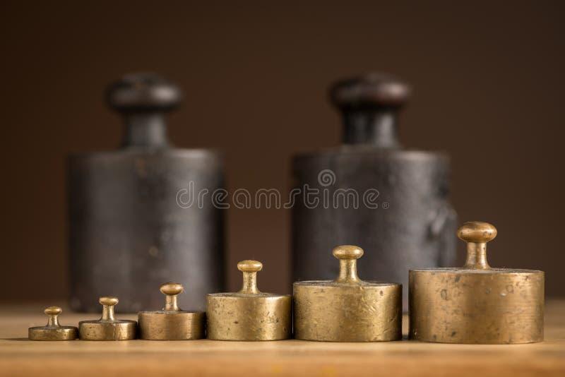 Viejos pesos del hierro 1kg y pesos de cobre amarillo más pequeños para una escala de la cocina imagen de archivo libre de regalías